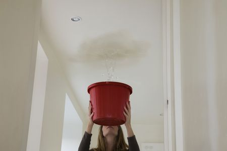 Woman trying to stop roof leak with bucket