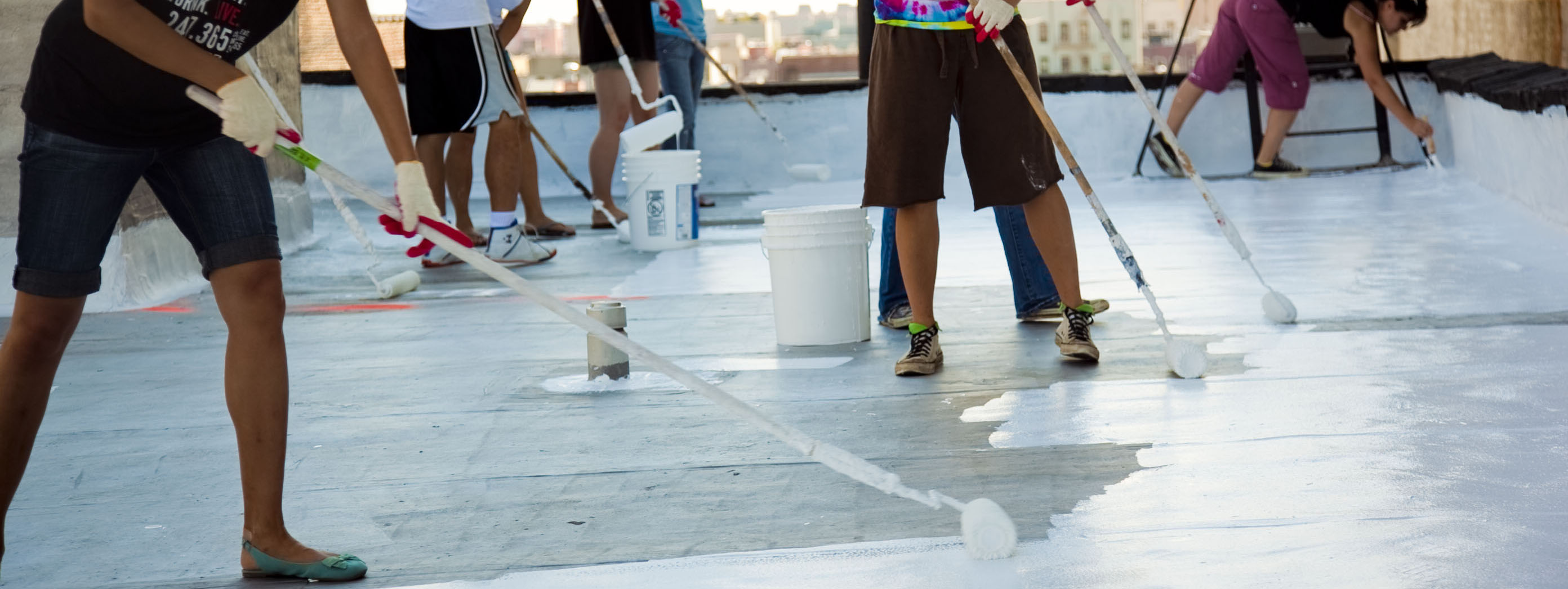 People painting a TPO roof